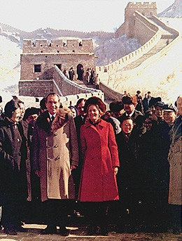 A photograph shows Richard Nixon, Patricia Nixon, and a host of officials standing in front of the Great Wall of China.