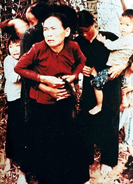 A photograph shows a group of Vietnamese women and children holding one another tightly, with looks of terror on their faces.