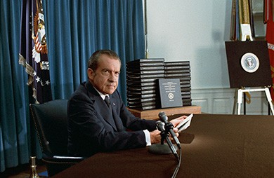 A photograph shows President Nixon seated at a desk by several microphones, holding papers as he prepares to address the nation.