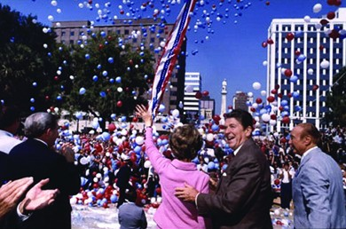 A photograph shows Ronald and Nancy Reagan on the campaign trail. They stand amidst a cheering crowd, surrounded by red, white, and blue balloons. Nancy Reagan waves to the crowd; Ronald Reagan smiles and places a hand on her back.