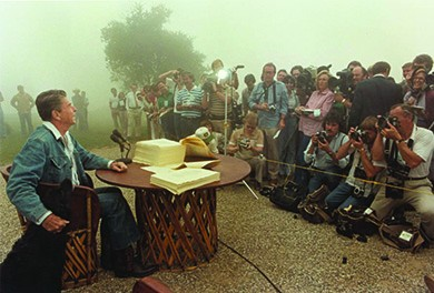 A photograph shows Ronald Reagan signing legislation while seated outdoors at a rustic table. He is dressed in blue jeans, a denim jacket, and cowboy boots, and he strokes the head of a large black dog seated beside him. In front of Reagan, the press takes photographs.