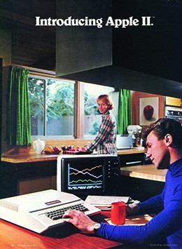An advertisement shows a young man seated at a kitchen table working on a 1970s-style computer. A woman, who is preparing food at the kitchen counter, looks over her shoulder at him and smiles.