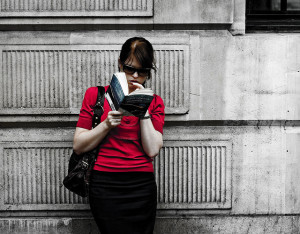 Photo of woman in a red shirt reading a novel while leaning against a gray concrete wall