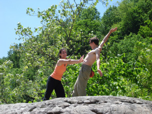 Photo of a woman playfully pretending to shove a shirtless man off of a rock cliff, surrounded by trees