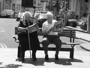 Black and white photograph of two people sitting on a bench near a street, reading newspapers