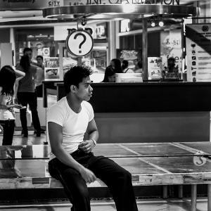 Black and white photo of a young man sitting in front of a City Information booth, so that the question mark sign is positioned directly over his head like a thought balloon.