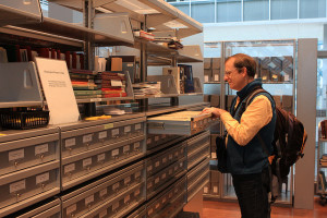 Photo of a man using a card catalog in a library