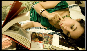 Photo of a woman lying on her side reading a book, with a pile of other books near her head.