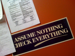 """Photo of papers on a desk, with a bumper sticker reading """"Assume Nothing Check Everything"""""""