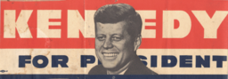 """In bumper sticker format, the top line reads """"Kennedy"""" in white font against a red background. The lower line reads """"FOR PRESIDENT"""" in blue font against a white background. Kennedy's smiling head is superimposed over the words in the middle of the sticker."""
