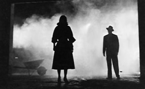 A still shot from a black and white 1940's movie is shown. We see the profile of a woman's full body in the center of the screen, and a man further away on the right. Mist billows behind them, and the contrast is high between black and white.
