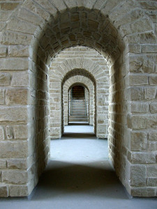 Photo looking down an open corridor, showing a series of stone archways leading to a set of stairs in the distance