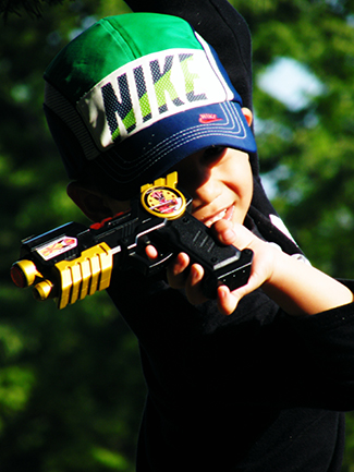 A photograph shows a child pointing a toy gun.