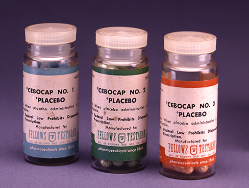 A photograph shows three glass bottles of pills labeled as placebos.