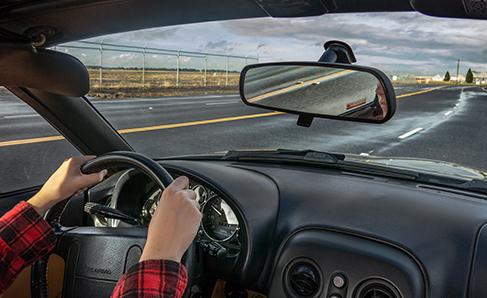 A photograph shows a person driving a car.
