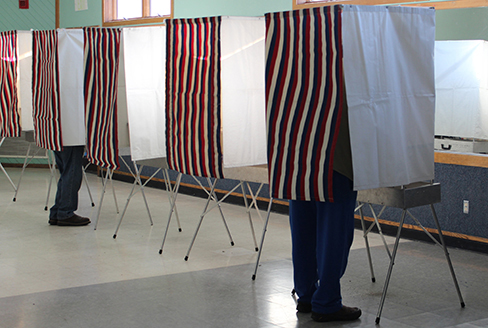 A photograph shows a row of curtained voting booths; two are occupied by people.