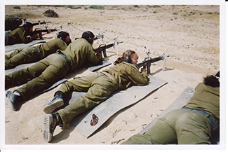 A photograph shows an armed female soldier among a group of soldiers.