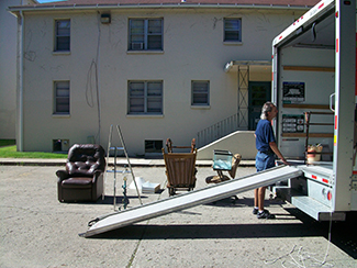 A photo shows a person next to the back of a moving truck unloading furniture.