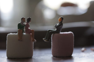Three small seated figurines posed as if in conversation. Two sit on a sugar cube on the left, one on a sugar cube on the right.