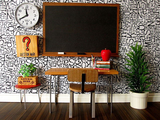 Miniature scene of a desk, chalkboard, plant, wall clock, and other classroom materials