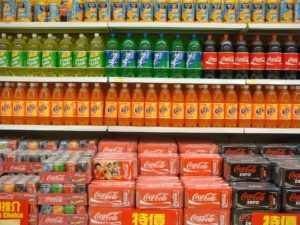 Multiple shelves of different colors, sizes, and types of soda