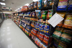 Aisle at the grocery store with shelves filled with bags of chips.