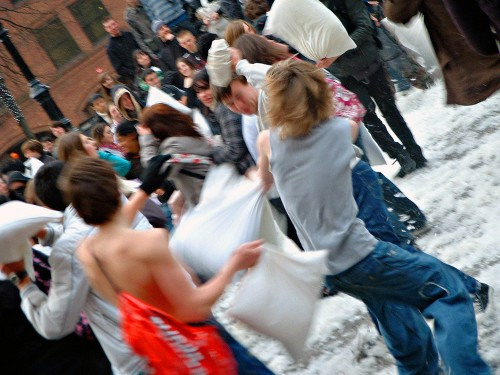 People having a pillow fight outdoors are shown here.