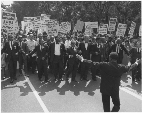 Figure (b) shows a large group of marchers for civil rights.