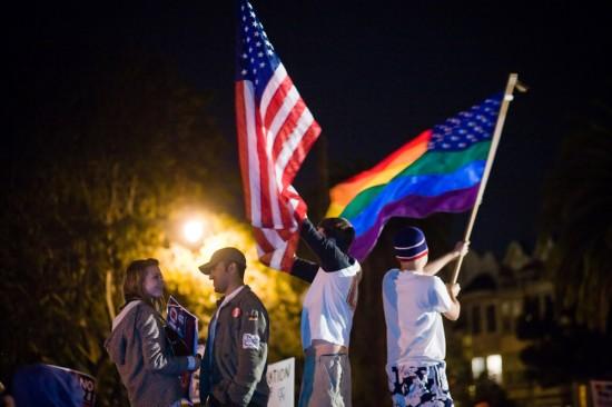 Figure (c) shows people waving a U.S. flag and a rainbow flag.