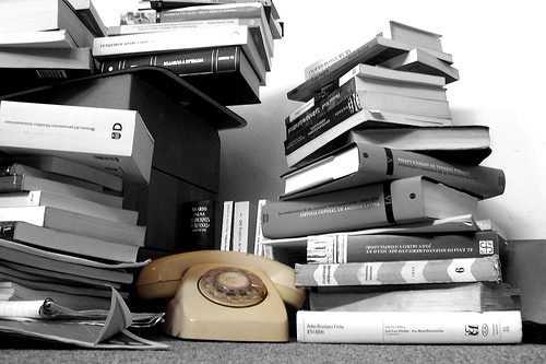 Black and white photo of a stack of books and textbooks.