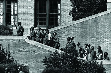A photograph shows uniformed soldiers holding rifles as they escort the Little Rock Nine up the steps of Central High School.