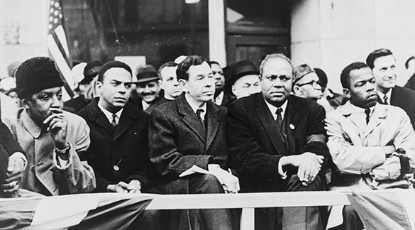 A photograph shows Bayard Rustin, Andrew Young, William Fitts Ryan, James Farmer, and John Lewis sitting in the front row of a large group of people.