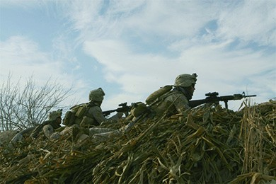 A photograph shows several Marines in position behind a hill, with their guns poised for attack.