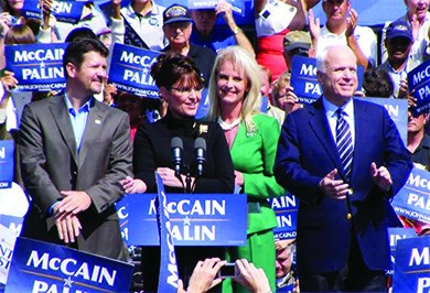 """A photograph shows John and Cindy McCain and Sarah and Todd Palin standing at a lectern, surrounded by supporters holding """"McCain / Palin"""" signs."""