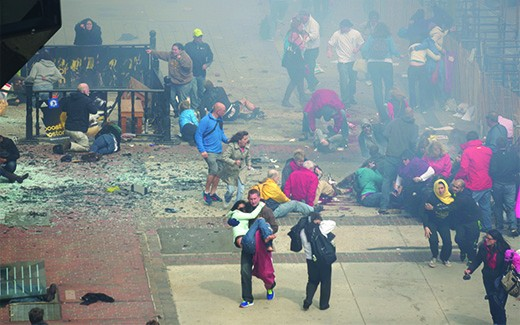 A photograph shows bystanders at the finish line of the Boston Marathon, tending to the injured and carrying them to safety.