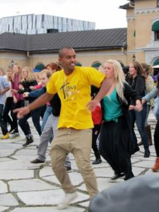 A large group of people dance in public in a flash mob