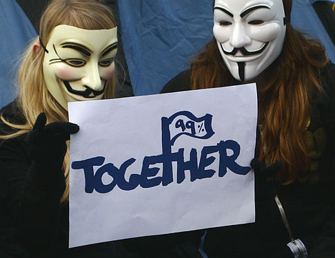 Two masked members of occupy wall street hold a sign reading 99% together