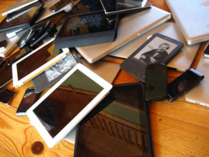 A large number of tablets, phones, and e-readers are piled up