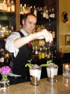 A bartender makes a drink.