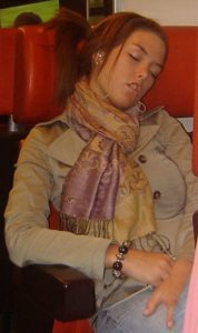 A woman is sleeping on a train.