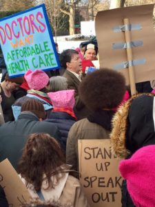 A group of protesters hold signs while gathered around a congressman.