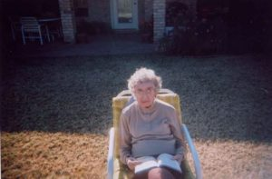 An elderly woman is sitting in a lawn chair