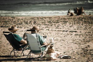 An old couple sits in chairs on a beach