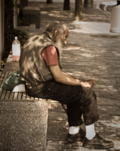 An old homeless man sits on a bench in Boston