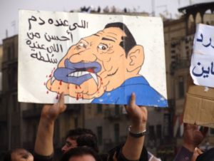 An Egyptian protester holds up a sign of Hosni Mubarak as a vampire