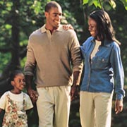 A smiling man and woman take a walk with their young daughter.