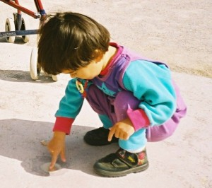 A young child plays with their finger in the dirt.
