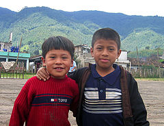 Two boys smiling outside of what appears to be their village school.