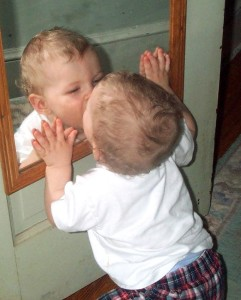 baby kissing his reflection in the mirror.