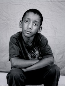 homeless boy looking reflectively at the camera for his picture, while he sits with his arms crossed in front of him on his knees.